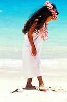 Girl in a white dress and wearing plumeria leis looks at her footprints in the sand at Lanikai Beach, Oahu.