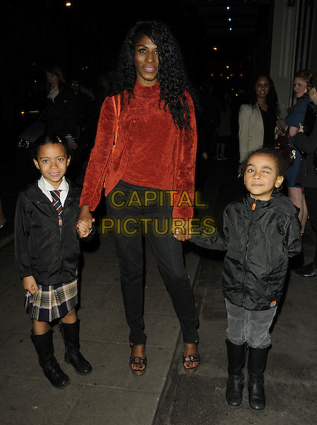 SINITTA aka Sinitta Renet Malone.The 'We Bought A Zoo' special screening, May Fair Hotel, Stratton St., London, England..March 15th, 2012.full length kids children daughter son mother mom mum family holding hands orange velvet top jacket black.CAP/CAN.©Can Nguyen/Capital Pictures.