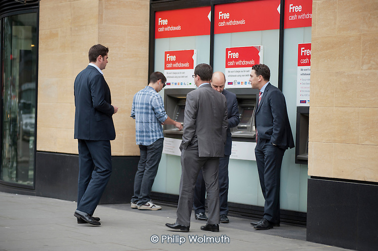 Free cash withdrawals.  City workers use a cash machine outside Deutsche Bank, London Wall, City of London.