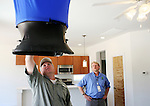 John Umphress, right, of Austin Energy, watches John Owens, a third party contractor from Austin Technical Services, conduct an air balance test as a part of Austin Energy's updated energy efficiency code in a new residential building on Tuesday, June 16, 2009 in Austin, Texas. The code that tests the energy efficiency of new buildings being constructed...
