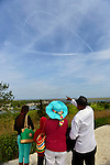 At Norman J Levy Park & Preserve, family members point south to contrails in the sky over Jones Beach where planes are performing in the Bethpage New York Air Show. Many visitors watched the air show from the marshland park after several major parkways to the famous Long Island beach were closed when it filled to capacity.