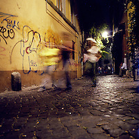Crowds walk through an alley in the Trastevere neighborhood in Rome, Italy in the summer of 2007.