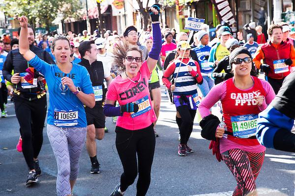Runners pass through the Williamsburg neighborhood of Brooklyn, New York during the 2014 TCS NYC Marathon on November 2, 2014.