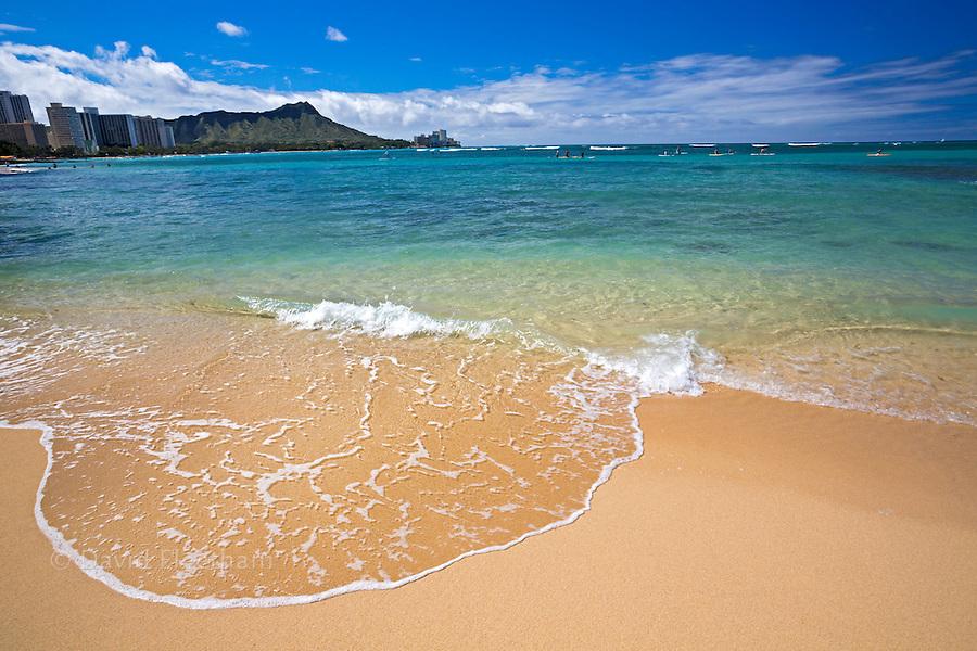 Waves wash up on Waikiki Beach with Diamond Head in the background, Oahu, Hawaii.