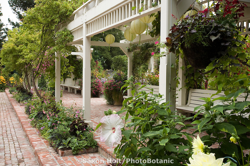 White painted pergola with benches covering brick walkway in California garden for outdoor living entertainment