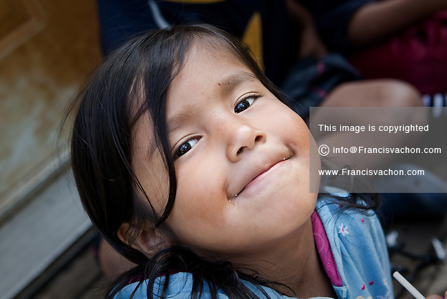 A young girl smiles to the photographer in the algonquin Anicinape community of Kitcisakik in Quebec, Canada, July 18, 2009. The aboriginals living in Kitcisakik, a small algonquin Anicinape community, don't have an official statue and are considered squatters by the crown. They don't have access to electricity and running water in their houses that are very modest.
