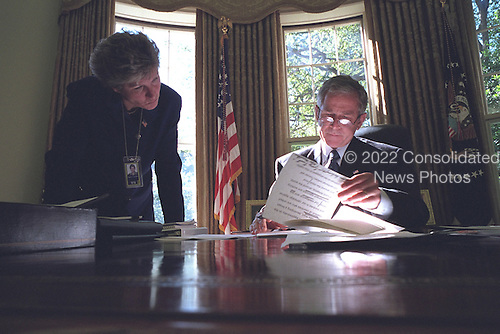 United States President George W. Bush looks over a brief with Counselor Karen Hughes in the Oval Office of the White House in Washington, D.C. on Monday, October 8, 2001..Mandatory Credit: Eric Draper - White House via CNP.