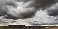 Ominous clouds hover over foothills of the Cedar Mountains west of Salt Lake City, Utah.