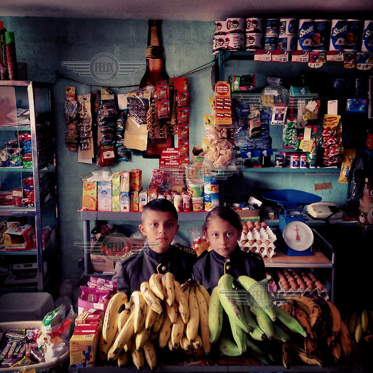 Antony Benavides, 10, and his sister, Ariana, 7, stand in their military school uniforms in Rosita's store in Tumbaco.