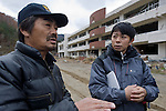 Takeshi Tachibana (R) and Hiromitsu Ito of Oh! Guts! stand next to the junior high school that was severely damaged by the march 2011 disasters in Ogatsu, Ishinomaki, Miyagi Prefecture, Japan on 01 Dec 2011. .Photographer: Robert Gilhooly