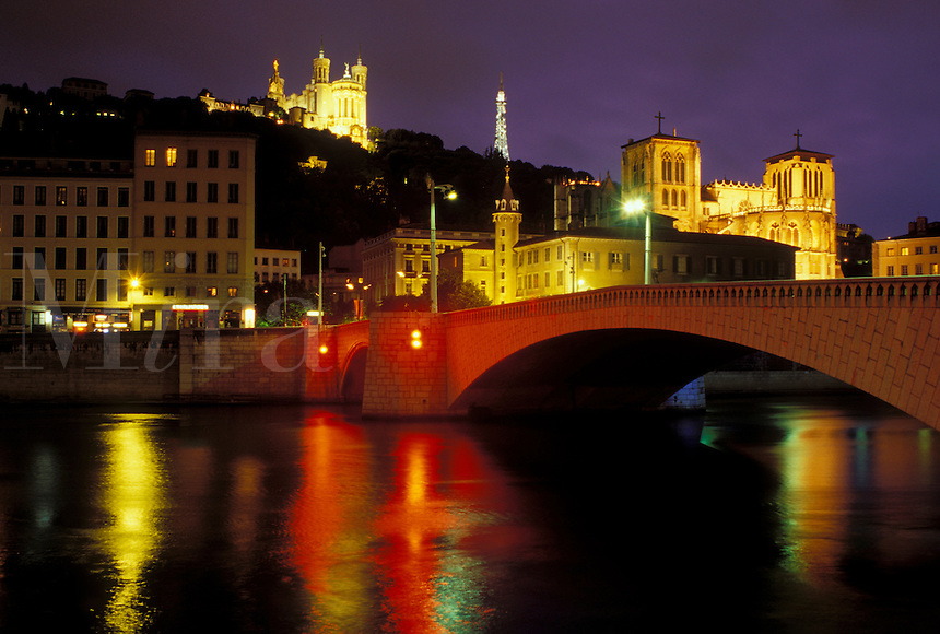 Lyon, Rhone-Alpes, France, Europe, Cathedral Saint Jean (below) and Basilique Notre Dame de Fourviere (above) illuminated at night along the Saone River in Lyon.