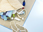 A straw mat and a bag filled with beach items--towel, lotion, books, and sandals