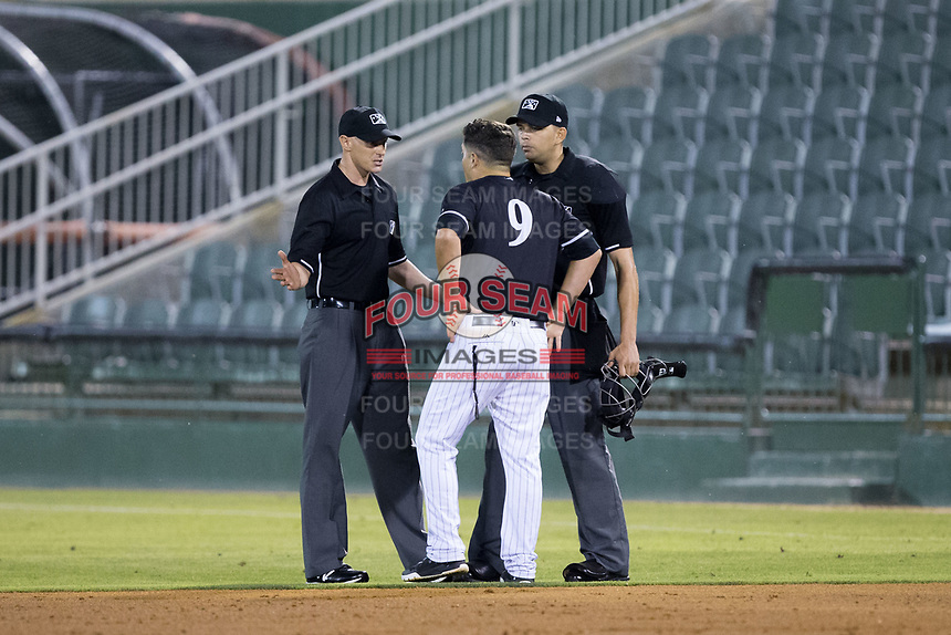 Kannapolis Intimidators manager Justin Jirschele (9) argues a call with base umpire Mike Snover (left) and home plate umpire Emil Jimenez during the game against the Hickory Crawdads at Kannapolis Intimidators Stadium on May 18, 2017 in Kannapolis, North Carolina.  The Crawdads defeated the Intimidators 6-4.  (Brian Westerholt/Four Seam Images)