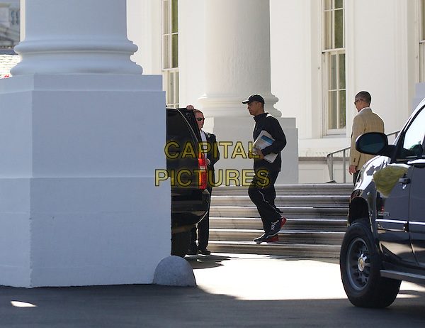 United States President Barack Obama walks out of the North Portico of the White House on his way to play basketball in Washington DC April 14, 2013.  .full length black baseball cap hat side profile tracksuit newspapers papers trainers sneakers .CAP/ADM/CNP/MR.©Molly Riley/CNP/AdMedia/Capital Pictures