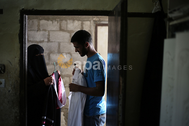 The mother of Fadi al-Shami, 21, a Palestinian blind youth, helps her son to wear his graduation suit at their home in Central Gaza Strip on Aug 17, 2013. al-Shami lost his sight after he was injured by an Israeli airstrike next to his family home at al-Musaddar village in central Gaza Strip during the Gaza–Israel conflict in 2006. Photo by Mahmoud Hamda