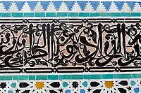 Fes, Morocco.  Attarine Medersa, 14th. Century.  Arabic Calligraphy in Tiles, Geometric Tile Work Underneath.