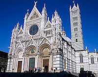 Siena, Tuscany, Italy<br /> Facade and ornate towers of Siena's Duomo, an 11th century Gothic style cathedral  against blue sky