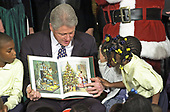 An unidentified little girl puts her hand on U.S. President Bill Clinton's hand as he read &quot;Twas The Night Before Christmas&quot; to a group of elementary school children at the White House in Washington, DC on December 19, 2000.<br /> Credit: Ron Sachs / CNP