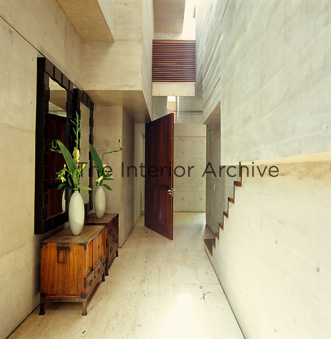 A pair of wooden sideboards, mirrors and vases of flowers furnish an otherwise stark concrete hallway