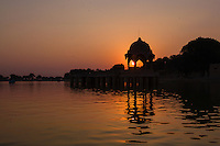 Stone tower in sacred Gadi Sagar lake in Jaisalmer, India during sunset