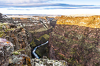 Bruneau River Canyon from it's namesake overlook.  This is a stunning eight-hundred foot deep chasm carved from the high desert of western Idaho. A fresh skiff of snow adds a bet of extra color to this already colorful landscape.  The river begins at the confluence of the Jarbidge River and the West Fork Bruneau River, and in the dense wilderness, plateaus are divided by staggering, meandering river canyons.