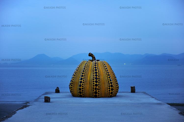 Yellow Pumpkin, a piece of art by Yayoi Kusama at dusk in Benesse Art Site. Naoshima. Setouchi Islands. Japan.