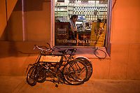Late-night patrons at El Preferido de Palermo. The cafe opened as an almacen, in 1952 when owner Arturo Fernandez arrived from Asturias, the province on Spain's lush north coast. Still teeming with shelves of canned eel, olives, and good wines, the grocery shares tight space with trendy orange and green tables where a limited menu is served to Palermo's young and hip. A photo of Francis Ford Coppola graces the counter, but the barrio's real luminary, Jorge Luis Borges (the street bears his name), lived across the way from 1901 to 1914. (Kevin Moloney for the New York Times)