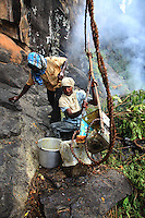 At the foot of the cliff, part of the team collects the pole and the container full of honey, conditions it for portage.