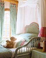 A child's bed has been covered with green and white gingham with curtains and table cover to match