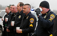 NWA Media/DAVID GOTTSCHALK - 12/18/14 - Rick Yeager,  right, officer with the city of Rogers Police Department, has a sip of hot chocolate as he listens to fifth grade students at Old Wire Road Elementary School sing as they participate in Caroling for Cops Thursday December 18, 2014 at the school in Rogers. The fifth graders  performed Christmas songs, handed out Christmas cards and served hot chocolate during the holiday program.