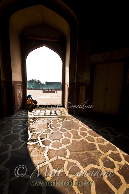 Two women sitting on the arched doorway of Humayun's Tomb.  Humayun was one of the great Mughal emperors who reigned during the 16th century.<br /> (Photo by Matt Considine - Images of Asia Collection)