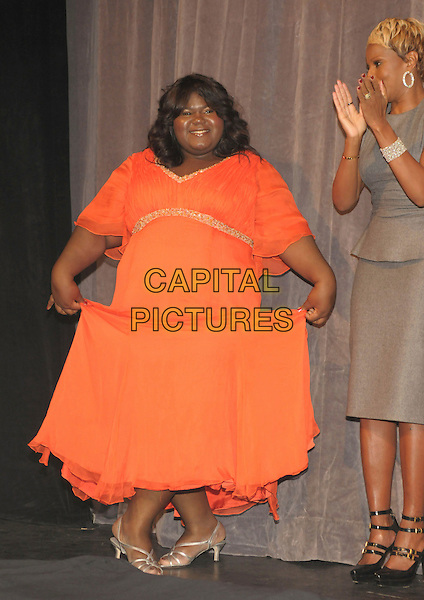 """GABOUREY SIDIBE & MARY J. BLIGE.Premiere of """"Precious: Based On The Novel """"Push"""" By Sapphire' during the 34th Annual Toronto International Film Festival, Toronto, Ontario, Canada, .13 September 2009..full length red coral orange dress overweight gold beaded trim curtsey on stage sandals clapping grey gray dress black shoes mary janes straps .CAP/ADM/BPC.©Brent Perniac/AdMedia/Capital Pictures."""