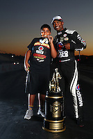 Nov 13, 2016; Pomona, CA, USA; NHRA top fuel driver Anson Brown (right) and son Adler Brown pose for a portrait with the world championship trophy following the Auto Club Finals at Auto Club Raceway at Pomona. Mandatory Credit: Mark J. Rebilas-USA TODAY Sports