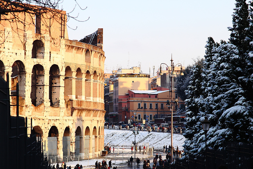 Rome, Fora:  A peculiar view of the back side (with respect to via dei Fori) of the Colosseum and of its surroundings, in the late afternoon, after a snowing night (February, 2012). There are quite a lot of people, too. One can see in particular a slope traced by persons that used it to slide, and trees almost completely covered by snow. This is an enlargement of a part of the original photo.