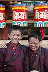 Kids standing in from of Buddhist prayer wheels, Paro, Bhutan