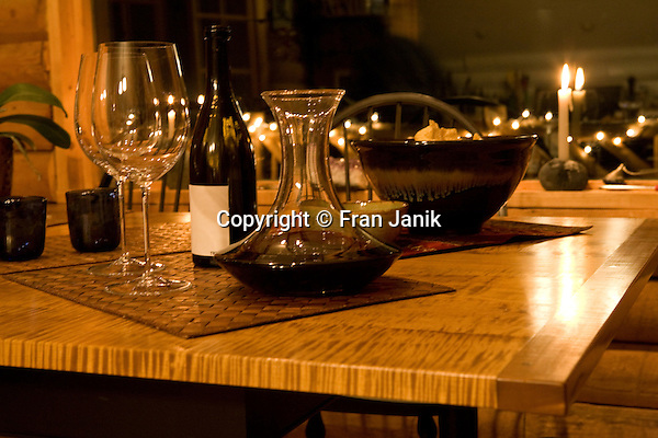 A fine red wine breathes in a glass decantor sitting on a tiger maple table. Wine glasses stand ready in this candle lit still life
