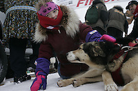 Ramey Brooks' daughter Molly pets one of her dad's dogs at the Nome finish line.     End of the  2005 Iditarod Trail Sled Dog Race.