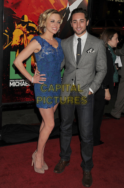 "Kelly Sullivan, Eric Schneider.HBO's ""Luck"" Los Angeles Premiere held at Grauman's Chinese Theatre, Hollywood, California, USA..January 25th, 2012.full length blue lace dress hand on hip grey gray suit jacket hand in pockets jeans denim.CAP/ROT/TM.©Tony Michaels/Roth Stock/Capital Pictures"