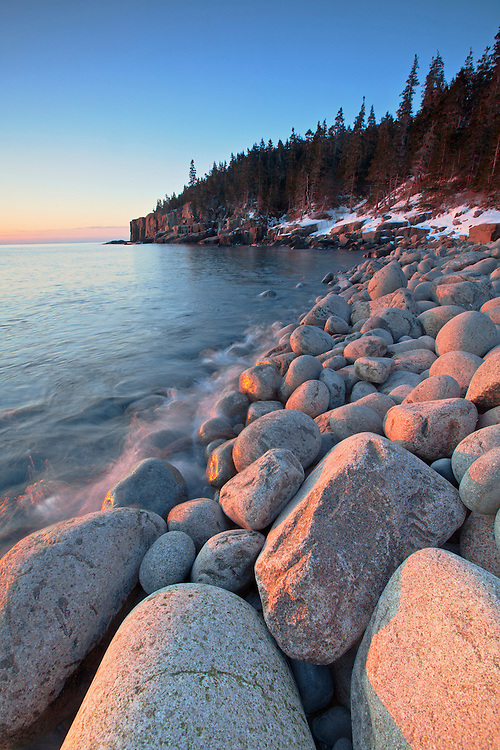 A golden winter sunrise illuminates the oversized boulders at Boulder Beach in Acadia National Park, Mount Desert Island, Maine, USA