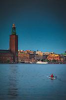 Kajak med kvinna på Riddarfjärden en sen sommarkväll med Stadshuset i Stockholm.
