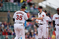 Rochester Red Wings manager Joel Skinner (35) takes the ball from pitcher Devin Smeltzer (21) for a pitching change during an International League game against the Charlotte Knights on June 16, 2019 at Frontier Field in Rochester, New York.  Rochester defeated Charlotte 3-2 in the second game of a doubleheader.  (Mike Janes/Four Seam Images)