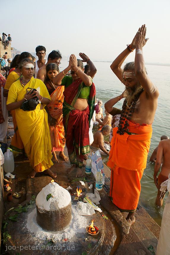 Hindu worshipper praying at a Shiva linga at the river Ganga, Varanasi.