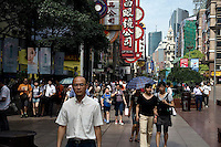 People walk down Nanjing East Road, a pedestrian walking area and one of the main shopping areas of Shanghai, China.