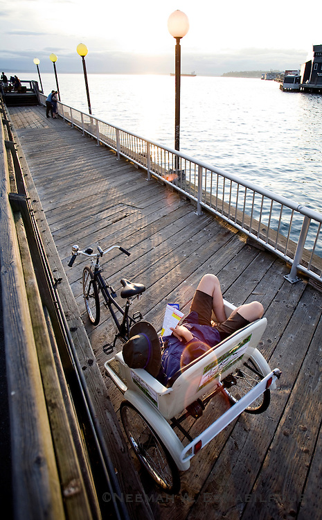A bike taxi driver reads a book while waiting for customers in Seattle, Washington.