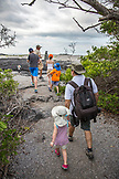 GALAPAGOS ISLANDS, ECUADOR, individuals walking through the trees toward the beach on Fernandina Island
