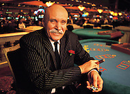 An older man sits at a craps table in a Las Vegas casino