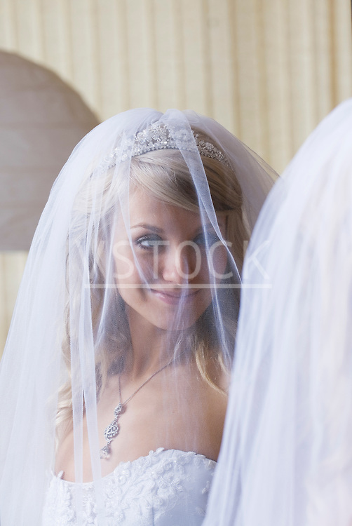 Bride wearing veil looking at herself in mirror