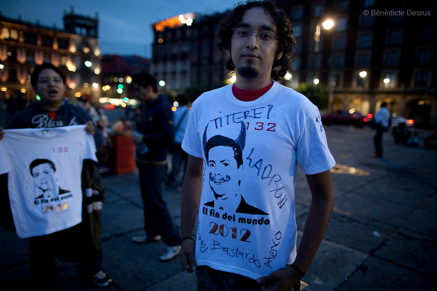 """30 June 2012 - Mexico City, Mexico - Vendors sells tshirt with Message """"132 Pena Nieto, the end of the World 2012"""". Thousands of demonstrators and university students members of the movement ?yo soy 132? (I am 132) hold candles during a demonstration to demand transparency in the next election at Zocalo square in Mexico City. """"YoSoy132"""" movement was organized by students against the candidature of Enrique Pena Nieto, presidential candidate of the opposition Institutional Revolutionary Party (PRI), who also demanded a balance in the media coverage of the presidential race. Mexico's presidential elections will take place on July 1. Photo credit: Benedicte Desrus"""