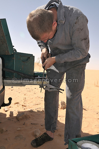 Africa, Tunisia, nr. Tembaine. Frank repairing a spring bush of his historic Series 2a Land Rover. --- No releases available, but releases may not be needed for certain uses. Automotive trademarks are the property of the trademark holder, authorization may be needed for some uses.  --- Info: Image belongs to a series of photographs taken on a journey to southern Tunisia in North Africa in October 2010. The trip was undertaken by 10 people driving 5 historic Series Land Rover vehicles from the 1960's and 1970's. Most of the journey's time was spent in the Sahara desert, especially in the area around Douz, Tembaine, Ksar Ghilane on the eastern edge of the Grand Erg Oriental.