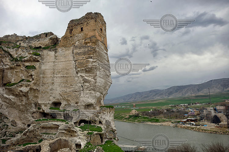 Old Hasankeyf Castle and cave houses above the Tigris River. 80% of the town of Hasankeyf will be submerged beneath 60 metres (200 feet) of water following the completion of the Ilisu hydroelectric dam, 96 kilometres (60 miles) downstream. The reservoir created by the dam will be approximately of 313 km2 (121 sq mi) and will flood several villages as well as Hasankeyf.